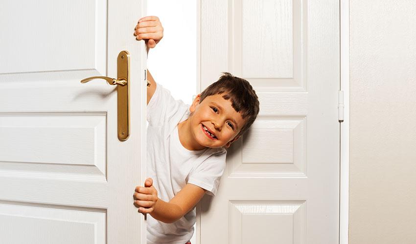 Lachend kind achter een deur,